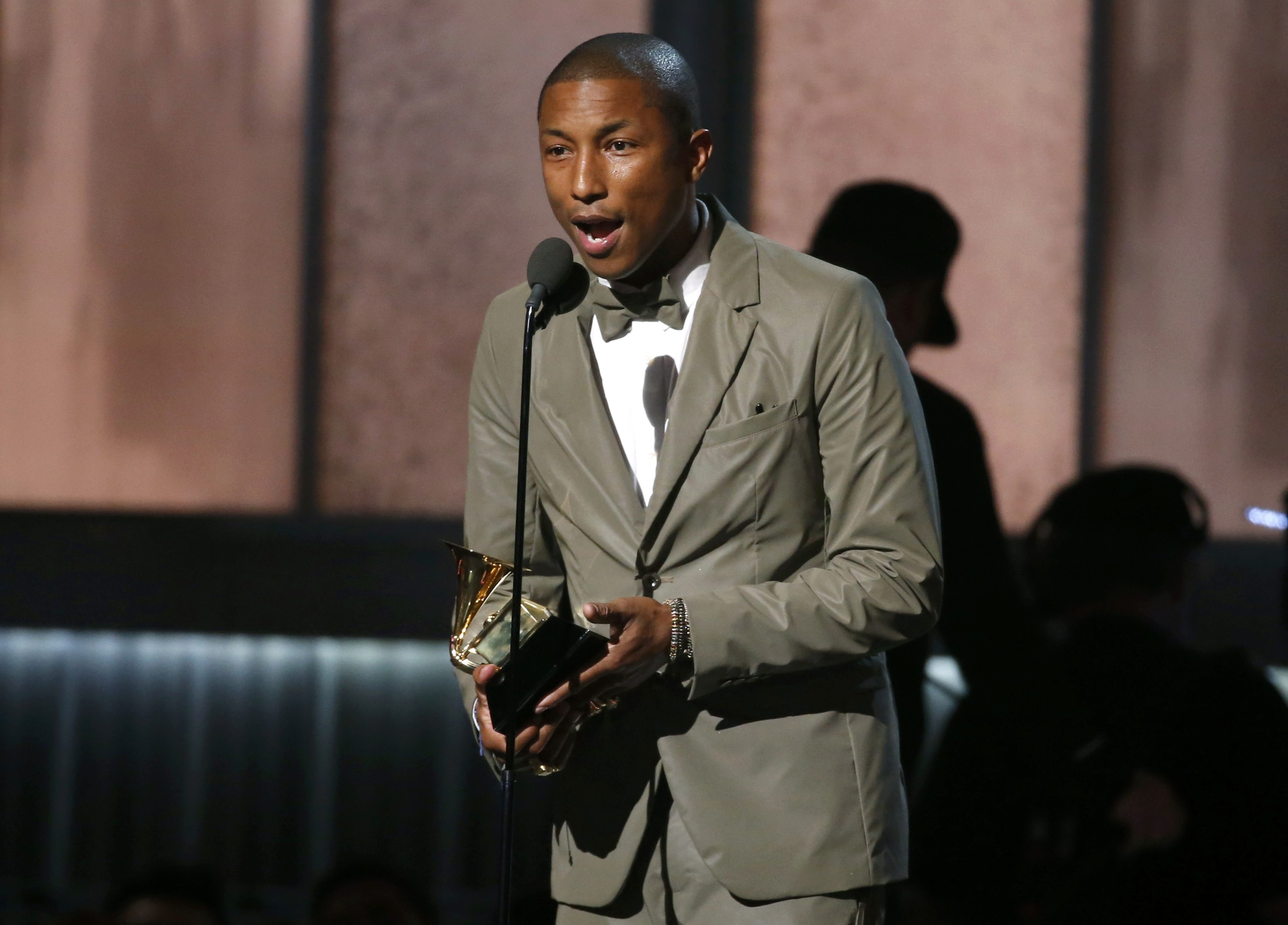 "Pharrell Williams accepts the award for best pop solo performance for ""Happy"" at the 57th annual Grammy Awards in Los Angeles"